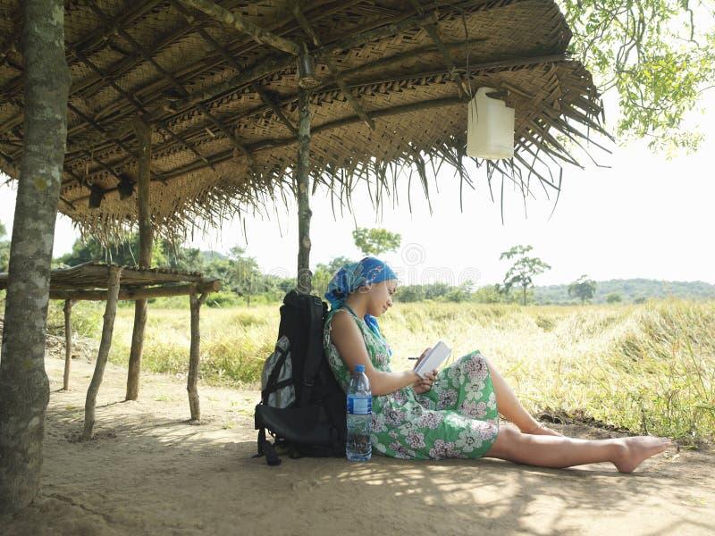 Żeński Turystyczny obsiadanie Pod buda dachem W polu fotografia royalty free