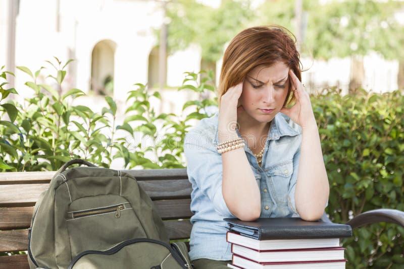 Żeński uczeń Outside z migreny obsiadaniem z książkami i plecy obraz royalty free