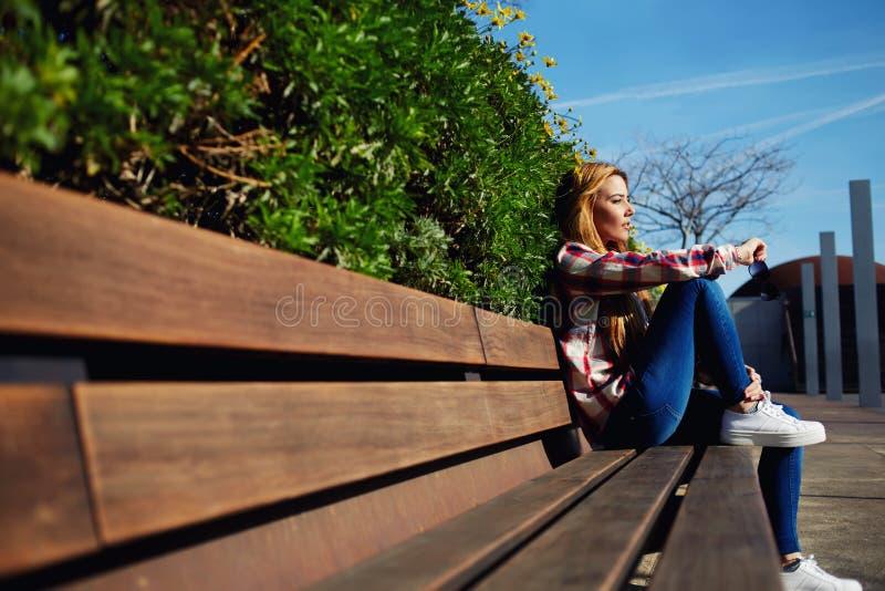 Żeński uczeń relaksuje przy kampusem podczas jej klasowej przerwy zdjęcie royalty free