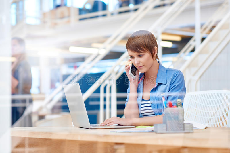 Żeński uczeń z telefonem pracuje na laptopie w nowożytnej przestrzeni zdjęcie stock