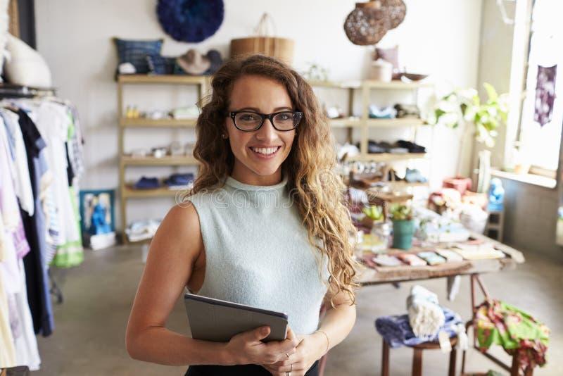Żeński właściciela biznesu mienia pastylki komputer w odzieżowym sklepie zdjęcie stock