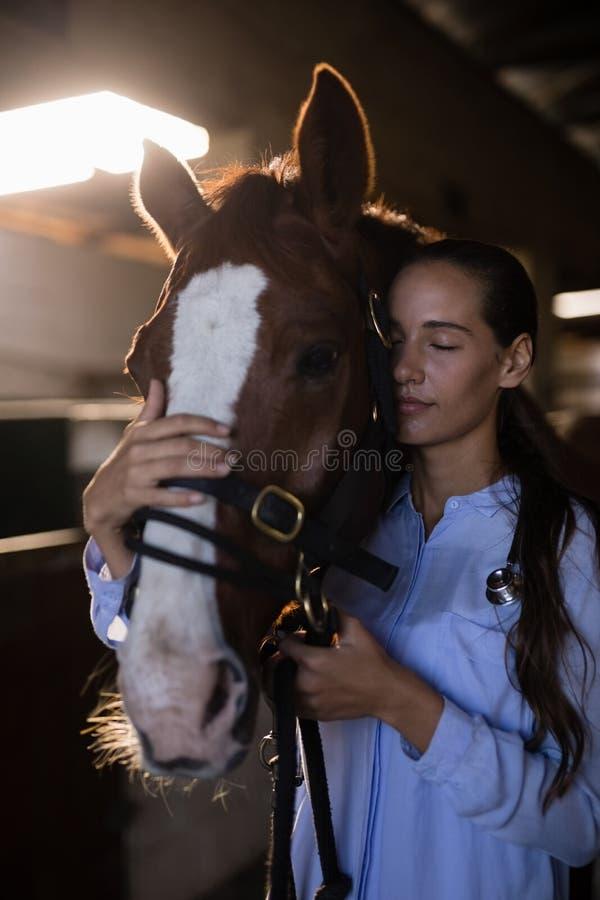 Żeński weterynarz z oczami zamykał pozycję koniem przy stajenką obrazy stock