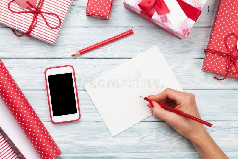 Żeński writing kartka z pozdrowieniami i opakunkowi boże narodzenie prezenty fotografia royalty free
