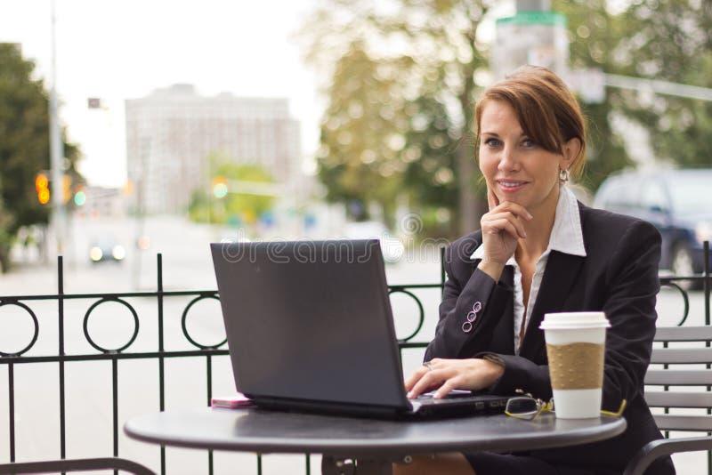 Żeński wykonawczy działanie outdoors przy kawiarnią zdjęcia stock