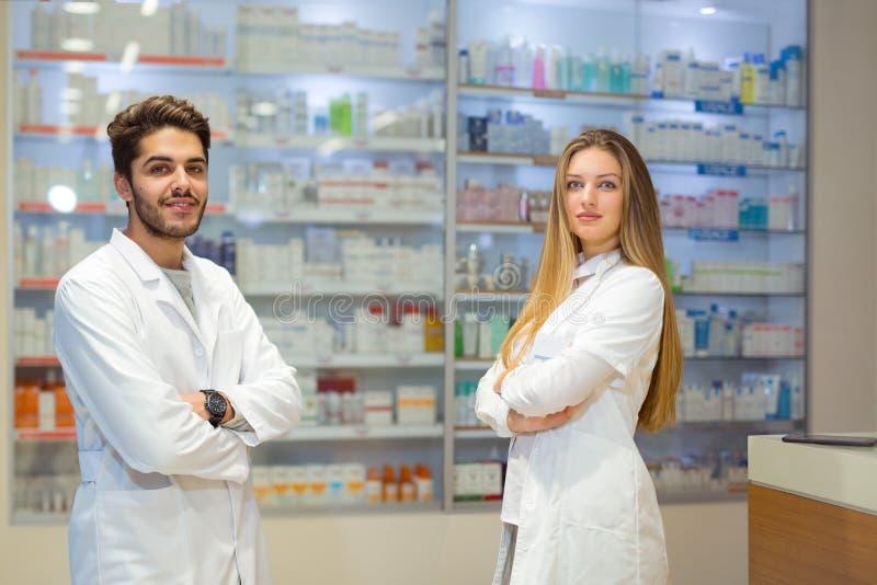 Żeńskie i męskie farmaceuty w aptece obrazy stock
