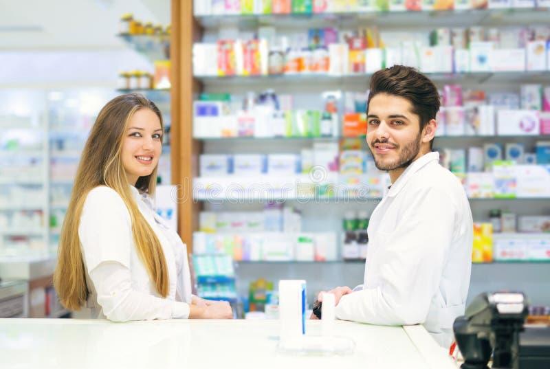 Żeńskie i męskie farmaceuty w aptece zdjęcie stock
