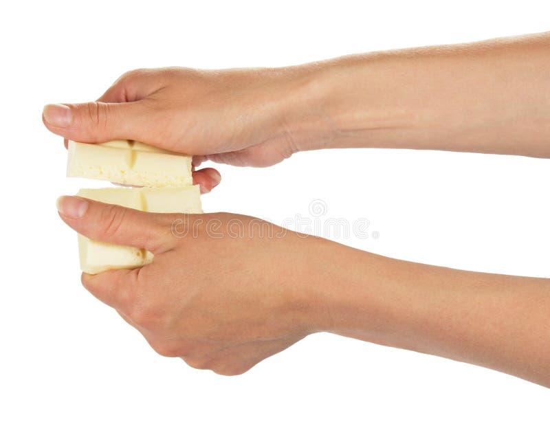 Żeńskie ręki łamają baru odizolowywającego biała czekolada obrazy stock