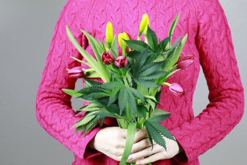 Żeńskie ręki trzymają bukiet tulipany, marihuana zieleni świezi liście, konopiana roślina z wiosna kwiatami (marihuana) zdjęcie stock