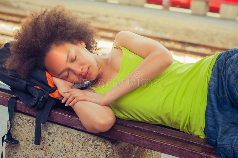 Żeńskiego backpacker turystyczny drzemanie na ławce fotografia stock