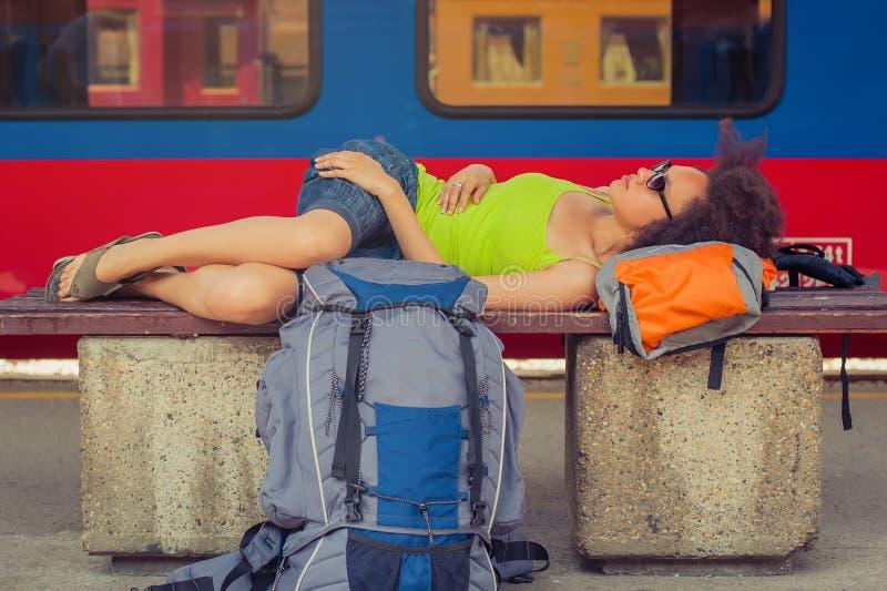Żeńskiego backpacker turystyczny drzemanie na ławce obraz stock