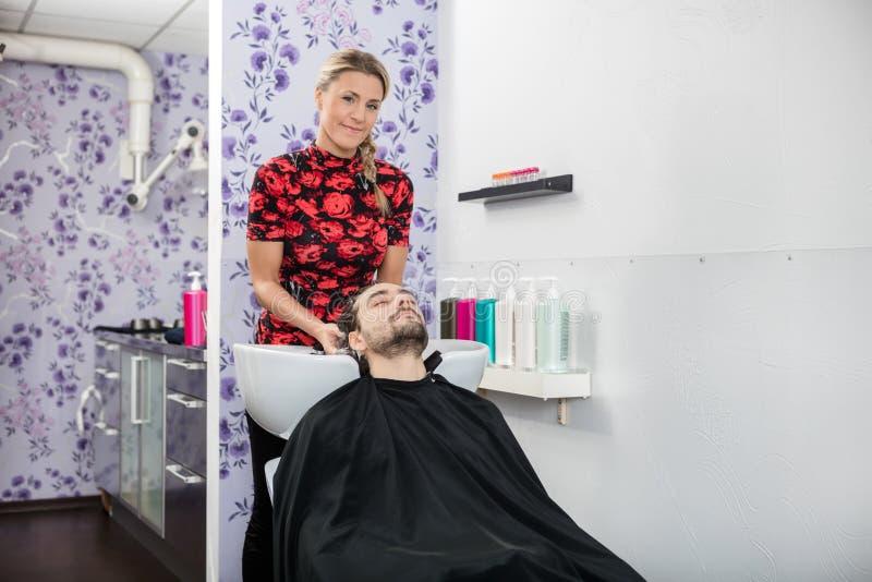 Żeńskiego fryzjera klienta Płuczkowy włosy W salonie obrazy royalty free