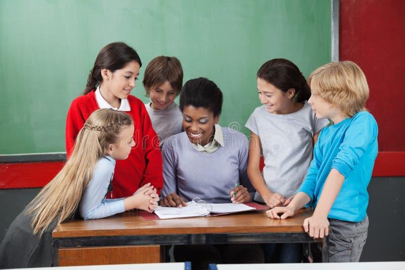 Żeńskiego nauczyciela nauczania ucznie Przy biurkiem fotografia royalty free
