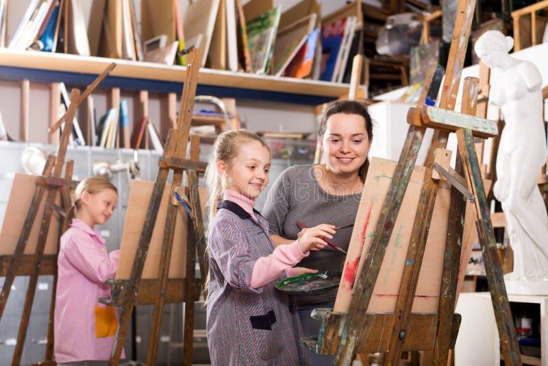 Żeńskiego nauczyciela pomaga dziewczyna podczas obraz klasy obrazy royalty free