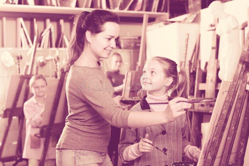 Żeńskiego nauczyciela pomaga dziewczyna podczas obraz klasy zdjęcia stock