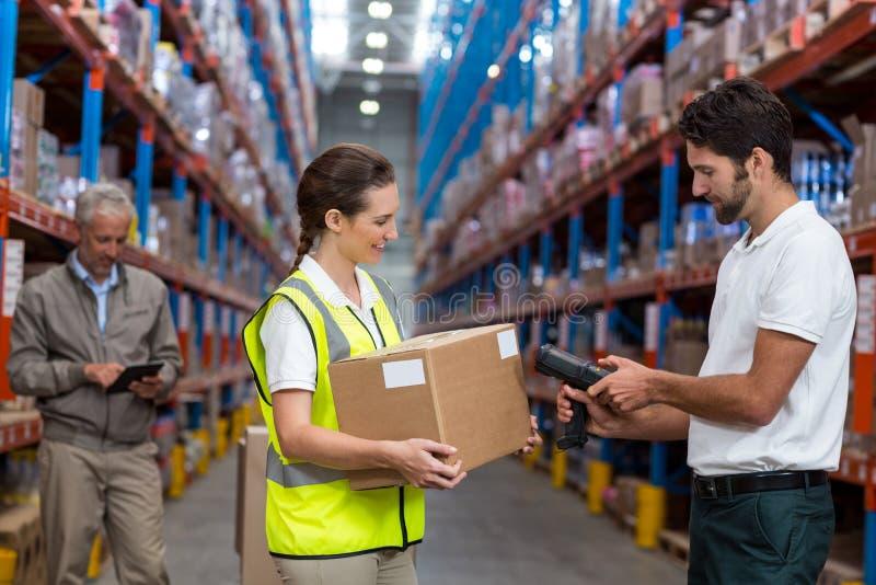 Żeńskiego pracownika mienia karton podczas gdy męski pracownika skanerowania barcode obraz stock