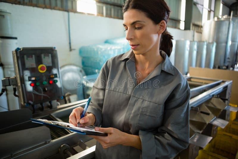 Żeńskiego pracownika writing na schowku w oliwnej fabryce zdjęcie royalty free