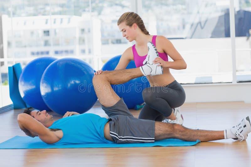 Żeńskiego trenera pomaga mężczyzna z jego ćwiczy przy gym zdjęcia stock
