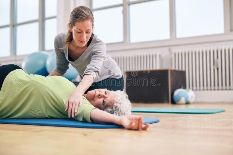 Żeńskiego trenera pomaga stara kobieta w rozciąganiu obrazy stock