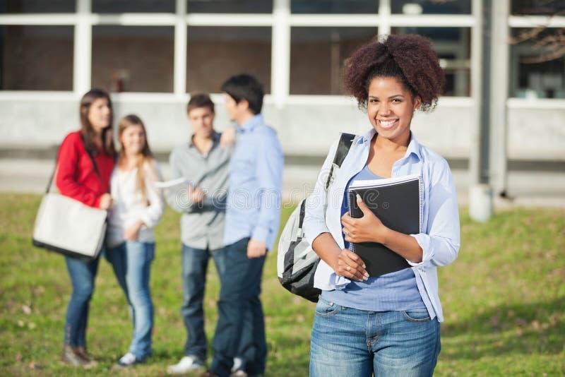 Żeńskiego ucznia mienia książki Na szkoła wyższa kampusie zdjęcia stock