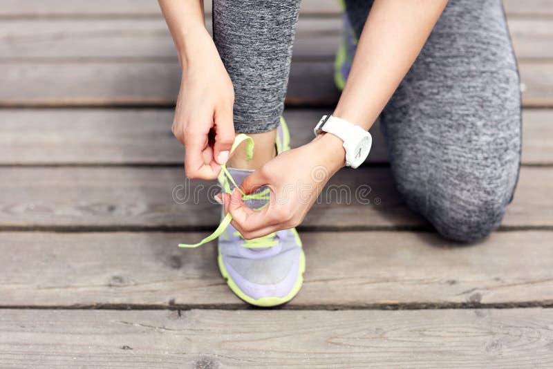 Żeńskiej atlety biegacz wiąże shoelaces zdjęcia royalty free