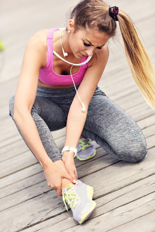 Żeńskiej atlety biegacza wzruszająca stopa w bólu outdoors obraz stock