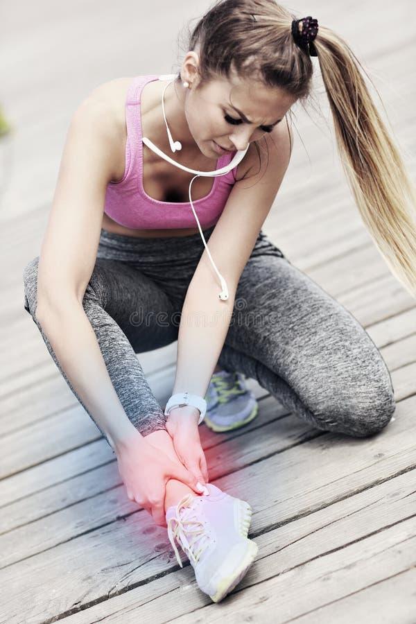 Żeńskiej atlety biegacza wzruszająca stopa w bólu outdoors fotografia stock