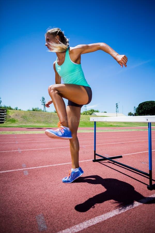 Żeńskiej atlety doskakiwanie nad przeszkoda obraz royalty free