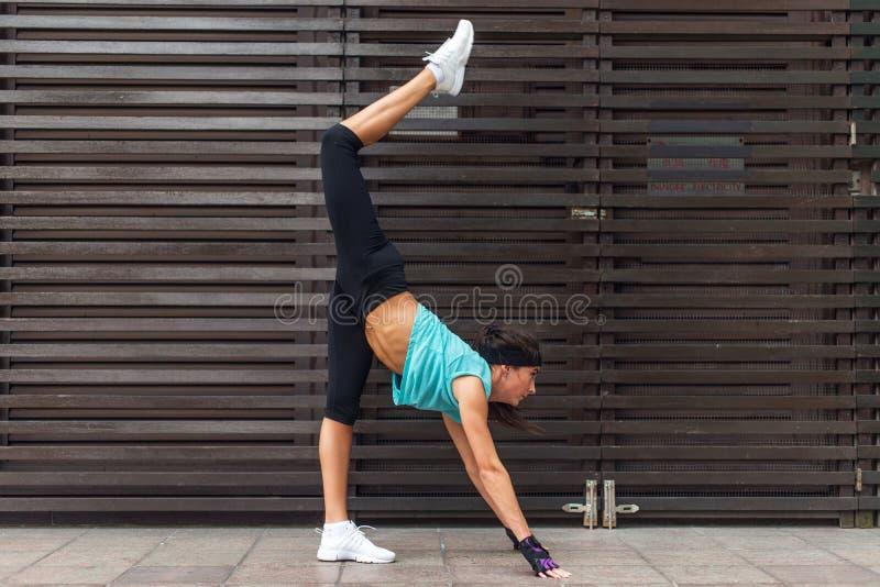 Żeńskiej atlety joga ćwiczy ćwiczenie rozciągać ona outdoors nogi Sporty młoda kobieta robi stojący rozszczepioną pozę dalej zdjęcia stock