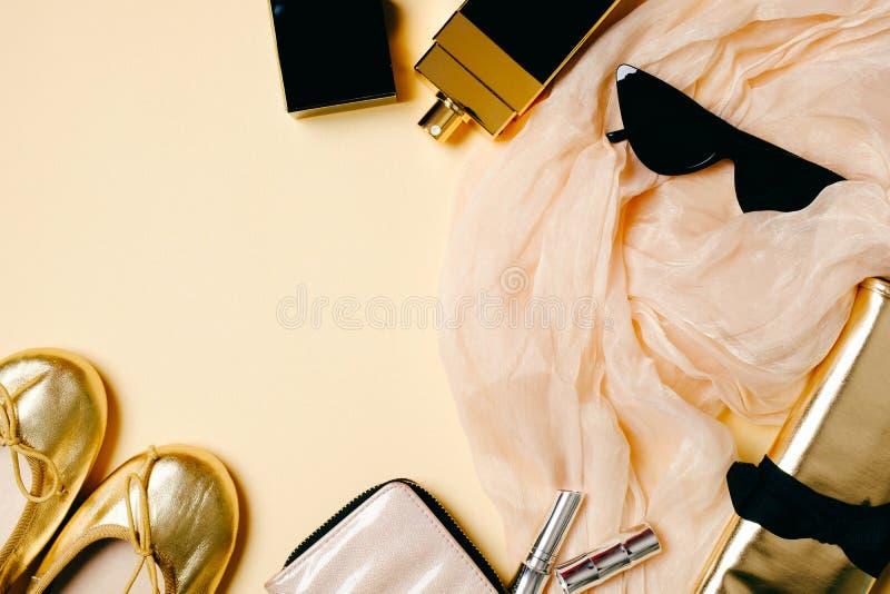 E Écharpe, lunettes de soleil, pantoufles d'or d'été, sac cosmétique, bouteille de parfum Le bureau des femmes image stock