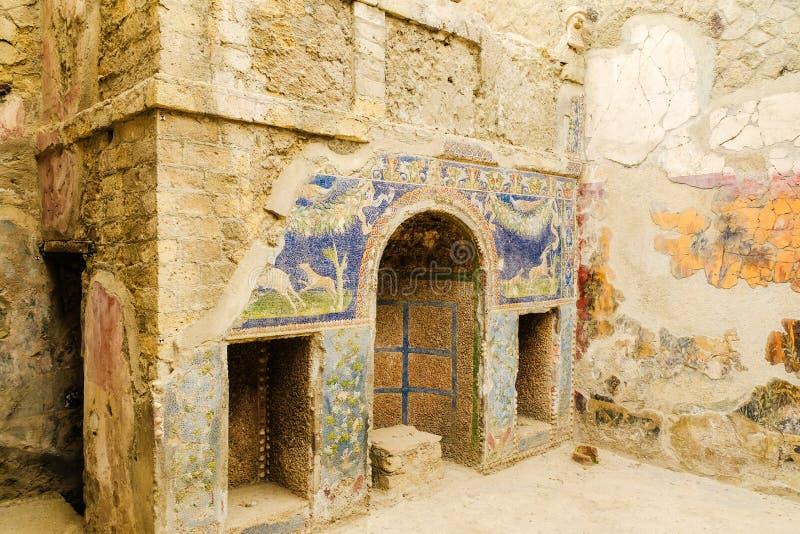 E Домашнее святилище со старыми римскими охотясь археологическими раскопками мозаики, Ercolano, Италией стоковое фото