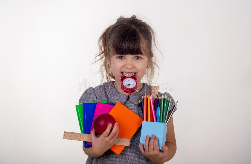 E Śliczny mądry dziecko trzyma szkolne dostawy w eyeglasses: pióra, notatniki, nożyce, budzik i jabłko, zdjęcia stock