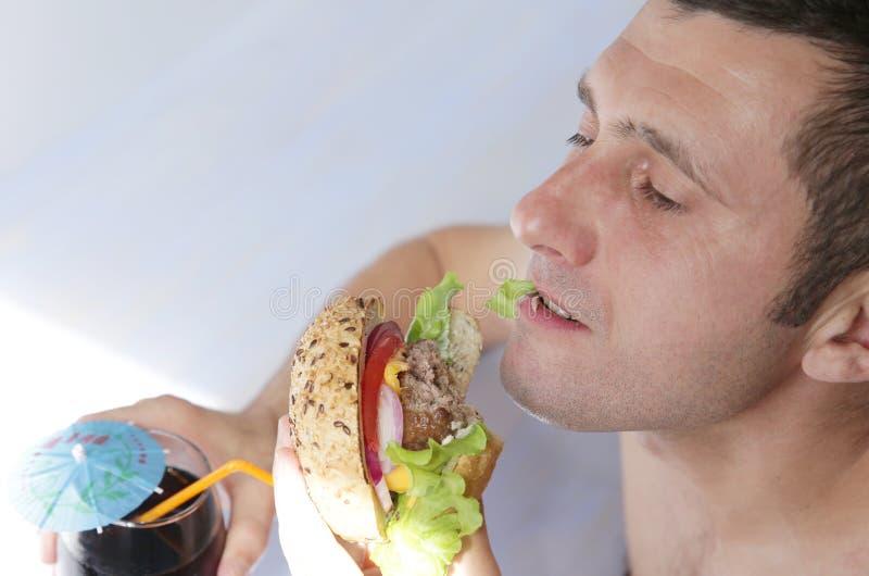 E Ένας πεινασμένος νεαρός άνδρας τρώει ένα μεγάλο σάντουιτς χάμπουργκερ με το βόειο κρέας, τις ντομάτες, τα κρεμμύδια, τη σάλτσα, στοκ εικόνες