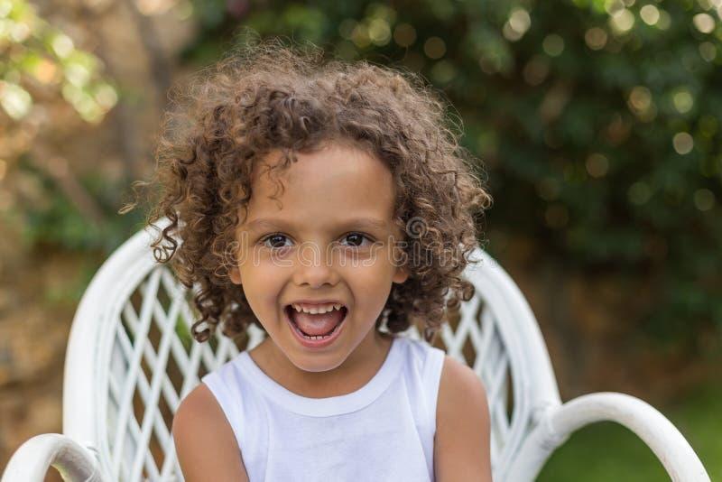 E Ένα πορτρέτο του χαμογελώντας μικρού παιδιού με τη σγουρή τρίχα στοκ εικόνα με δικαίωμα ελεύθερης χρήσης