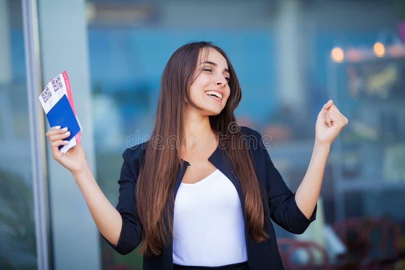 E Γυναίκα που κρατά το αεροπορικό εισιτήριο δύο στο εξωτερικό στο διαβατήριο κοντά στον αερολιμένα στοκ φωτογραφία