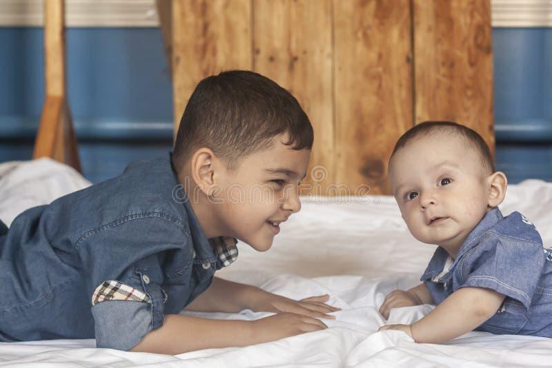 E Ευτυχές πορτρέτο αδελφών 6 έτη και αγόρια 6 μηνών που έχουν τη διασκέδαση Δύο παιδάκια που χαμογελούν έχοντας το αγαθό στοκ φωτογραφίες με δικαίωμα ελεύθερης χρήσης