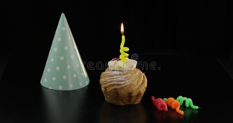 E Κέικ και εορταστικό κερί σε το Γιορτάστε τα γενέθλια στοκ φωτογραφίες
