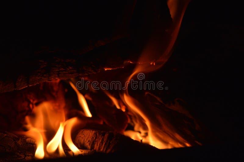 E Καίγοντας ξύλο στην εστία Φλόγα στο σκοτάδι στοκ εικόνα με δικαίωμα ελεύθερης χρήσης