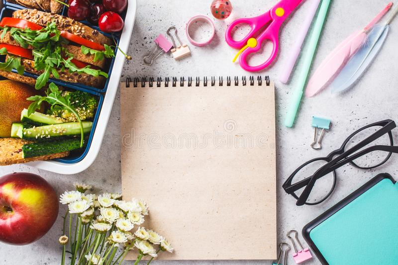 E Καλαθάκι με φαγητό με το σάντουιτς, τα φρούτα, τα πρόχειρα φαγητά, το σημειωματάριο, τα μολύβια και τα σχολικά στοιχεία, τοπ άπ στοκ φωτογραφίες