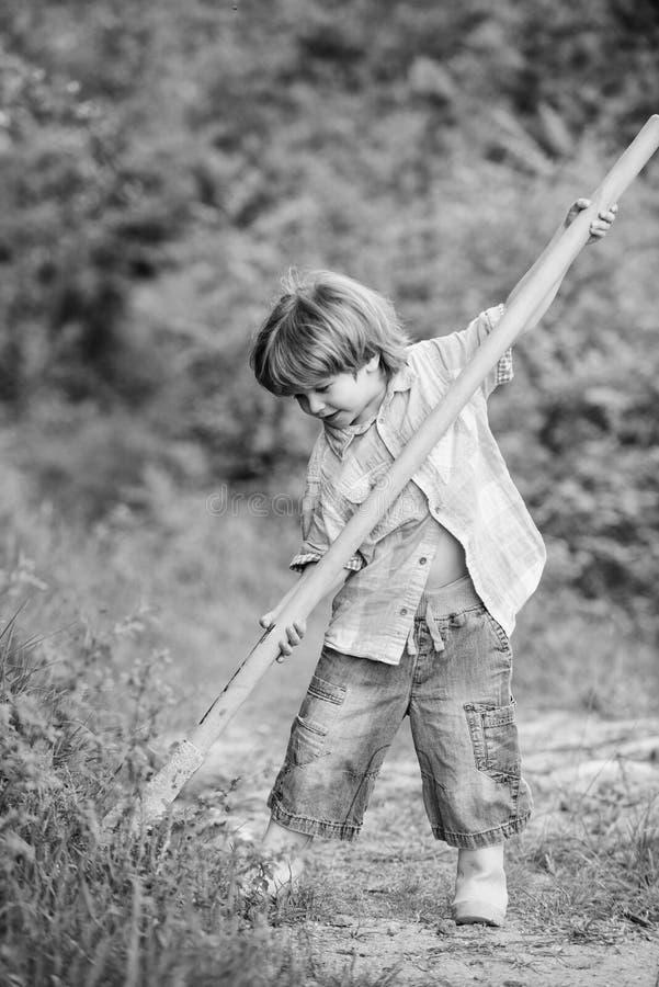 E Κυνήγι περιπέτειας για τους θησαυρούς Λίγος αρωγός που εργάζεται στον κήπο Χαριτωμένο παιδί στη φύση που έχει τη διασκέδαση με στοκ εικόνες