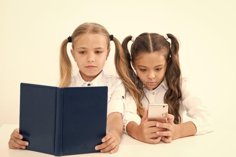E Να πάρει τις πληροφορίες Μικρά κορίτσια που διαβάζουν το βιβλίο εγγράφου και ebook στο smartphone Η σωστή επιλογή στοκ φωτογραφία με δικαίωμα ελεύθερης χρήσης