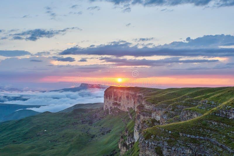 E Ο ήλιος ρύθμισης φωτίζει τη σειρά, την ομίχλη και τα σύννεφα βουνών στοκ φωτογραφίες