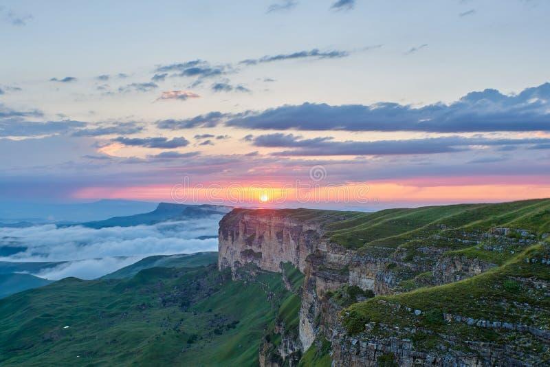 E Ο ήλιος ρύθμισης φωτίζει τη σειρά, την ομίχλη και τα σύννεφα βουνών στοκ φωτογραφία με δικαίωμα ελεύθερης χρήσης