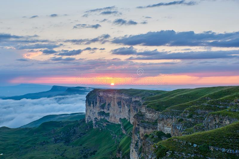 E Ο ήλιος ρύθμισης φωτίζει τη σειρά, την ομίχλη και τα σύννεφα βουνών στοκ φωτογραφία