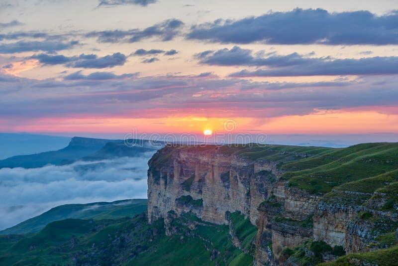 E Ο ήλιος ρύθμισης φωτίζει τη σειρά, την ομίχλη και τα σύννεφα βουνών στοκ εικόνες