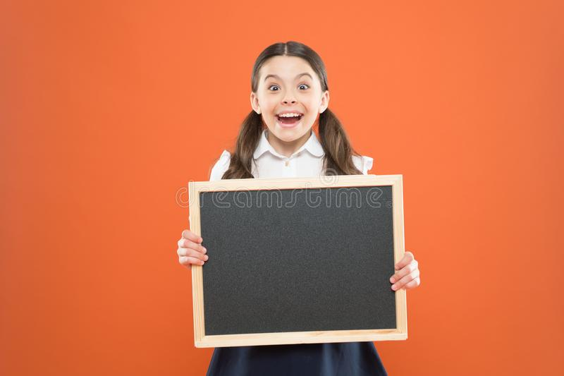 E πωλήσεις σχολικής αγοράς signage εύθυμο σχολικό κορίτσι με τον πίνακα ευτυχής μαθητής στη σχολική στολή o στοκ φωτογραφία