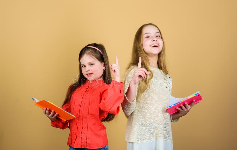 E σπουδαστές που διαβάζουν ένα βιβλίο Σχολικό πρόγραμμα μικρά κορίτσια με τα βιβλία σημειώσεων Φιλία και αδελφότητα r στοκ εικόνες