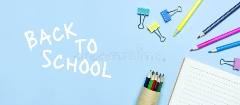E Τα ξύλινα χρωματισμένα μολύβια, καθαρό σχολικό σημειωματάριο στη γραμμή, συνδετήρες εγγράφου στο μπλε επίπεδο άποψης υποβάθρου  στοκ εικόνες