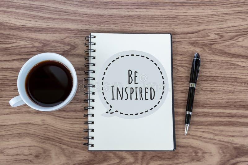 E Το εμπνευσμένο κινητήριο απόσπασμα εμπνέεται με το κείμενο σε ένα βιβλίο σημειώσεων, μια μάνδρα και ένα φλυτζάνι του μαύρου καφ στοκ εικόνες