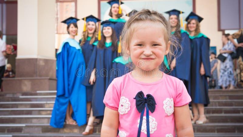 E Το πορτρέτο κινηματογραφήσεων σε πρώτο πλάνο του μικρού κοριτσιού σε μια ρόδινη μπλούζα, απόφοιτοι φοιτητές στέκεται στο υπόβαθ στοκ εικόνες