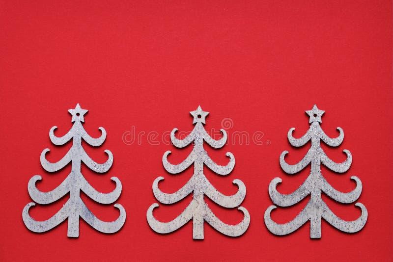 E Τρία διακοσμητικά χριστουγεννιάτικα δέντρα στο κόκκινο σκηνικό r r στοκ φωτογραφία με δικαίωμα ελεύθερης χρήσης